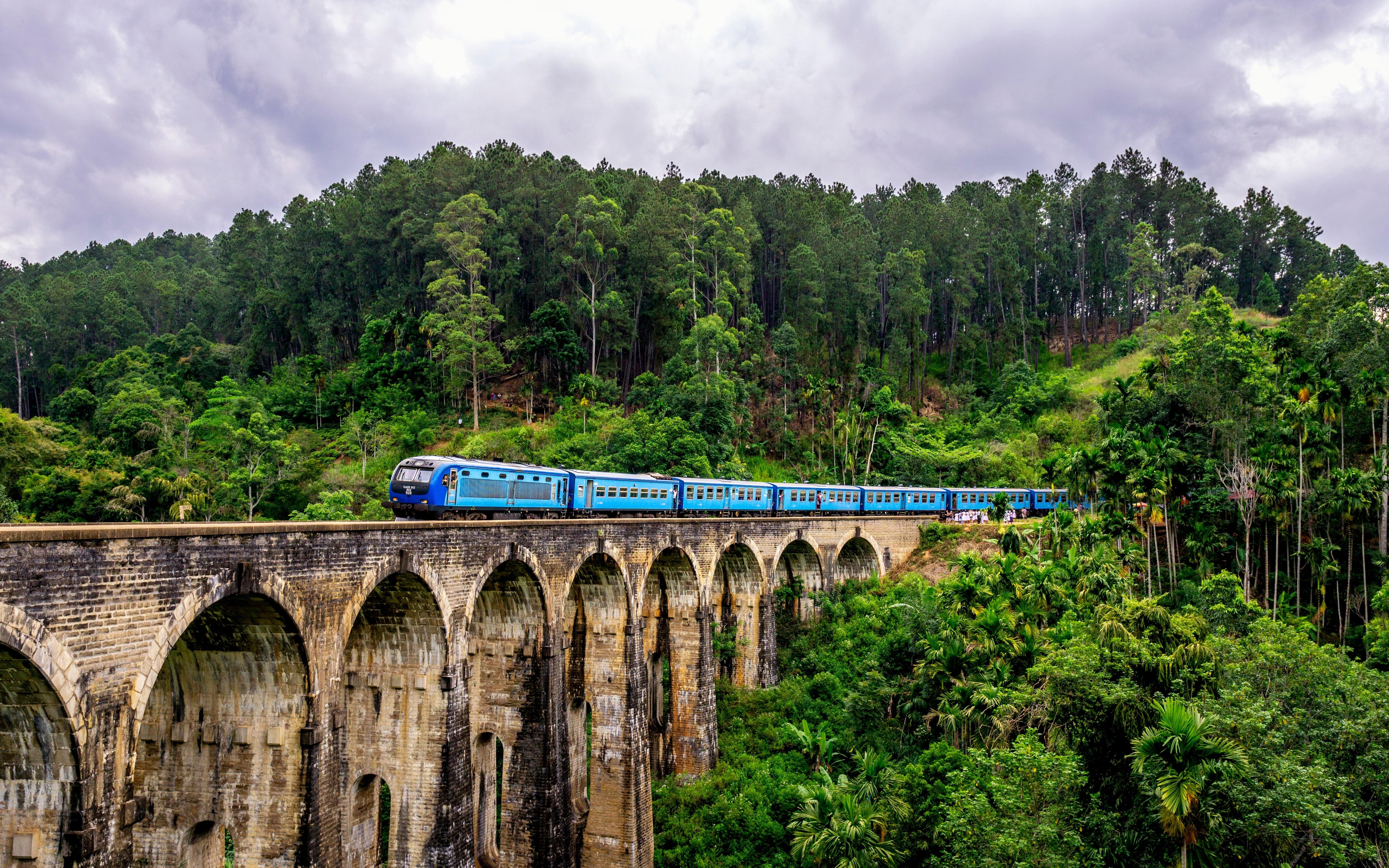 Traveling by train over Nine Arch Bridge in Sri Lanka