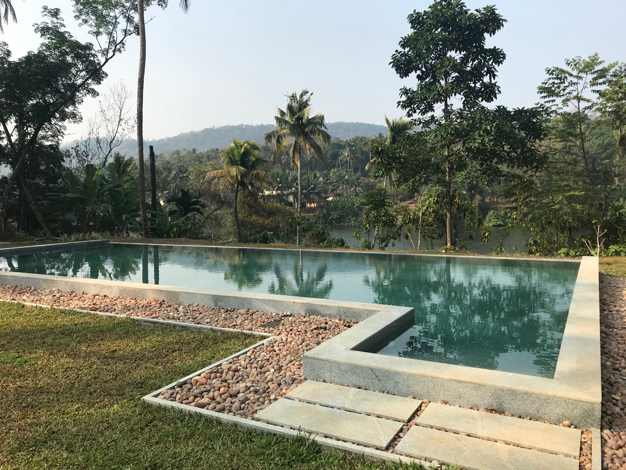 The pool at Windermere River House with views of the Periyar River